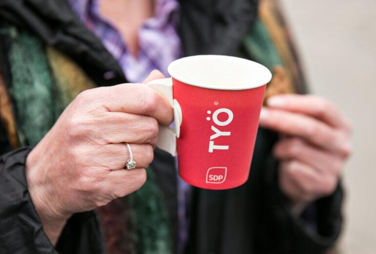 Kuva, jossa vanhat kädet pitelevät pahvista kahvikuppia, jossa lukee työ