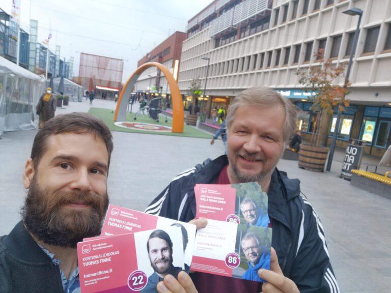Tuomas ja Kalle tallinnan aukiolla juuri painetut jäsenvaalimainokset käsissään.